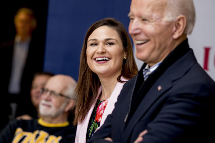 FILE - In this Friday, Jan. 3 2020 file photo, Democratic presidential candidate Joe Biden, right, and Rep. Abby Finkenauer, D-Iowa, center, smile during a campaign rally at the University of Dubuque, in Dubuque, Iowa. Iowa Democrat Abby Finkenauer is running for Republican Chuck Grassley's U.S. Senate seat. The one-term former congresswoman hopes her blue-collar credentials will propel her forward in a state that has grown more conservative over the years. (AP Photo/Andrew Harnik)
