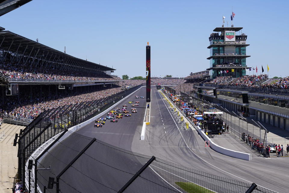 Scott Dixon, of New Zealand, leads the field into the first turn at the start of the Indianapolis 500 auto race at Indianapolis Motor Speedway in Indianapolis, Sunday, May 30, 2021. (AP Photo/Paul Sancya)