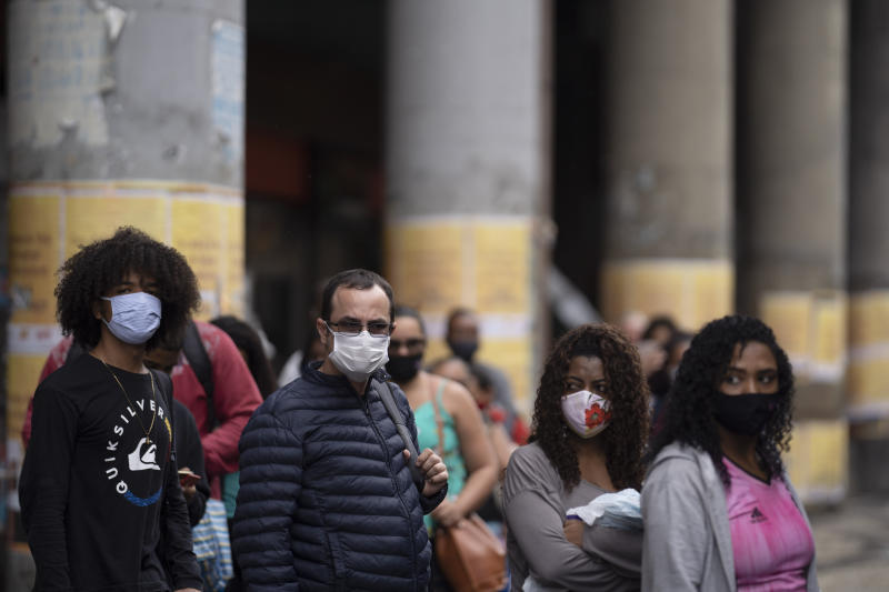 Wearing protective masks, commuters wait in line for a bus amid the new coronavirus pandemic in Rio de Janeiro, Brazil, Thursday, July 30, 2020. (AP Photo/Leo Correa)