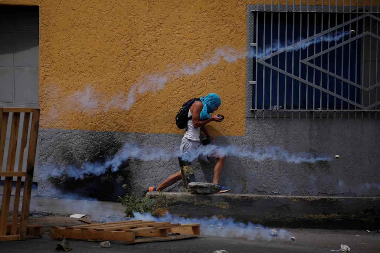 A demonstrator runs away from tear gas during a rally called by health care workers and opposition activists against Venezuela's President Nicolas Maduro in Caracas, Venezuela May 22, 2017. REUTERS/Carlos Barria     TPX IMAGES OF THE DAY