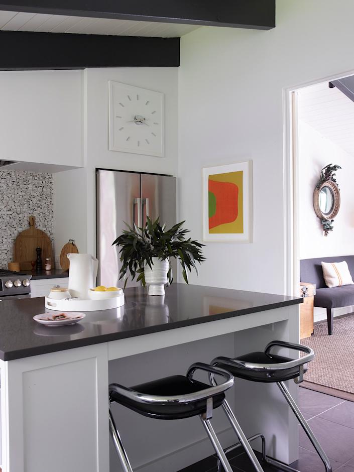 """<div class=""""caption""""> The kitchen of interior designer Matthew Patrick Smyth's Salisbury, Connecticut, weekend house features Cambria quartz countertops, a backsplash of Selvaggio Mosaics from <a href=""""https://www.annsacks.com/"""" rel=""""nofollow noopener"""" target=""""_blank"""" data-ylk=""""slk:Ann Sacks"""" class=""""link rapid-noclick-resp"""">Ann Sacks</a>, and circa-1970 barstools by Börge Lindau and Bo Lindekrantz for <a href=""""https://www.lammhults.se/"""" rel=""""nofollow noopener"""" target=""""_blank"""" data-ylk=""""slk:Lammhults"""" class=""""link rapid-noclick-resp"""">Lammhults</a>. """"The house was a mess before,"""" says Smyth, """"with layers of linoleum and avocado green appliances. Everything had to go."""" </div>"""