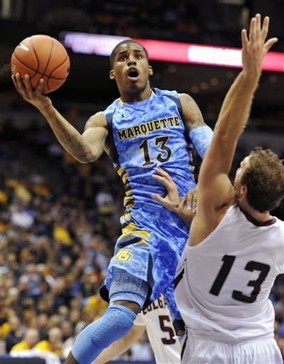 Marquette's Vander Blue (13) drives to the basket against Colgate's Murphy Burnatowski (13) during the first half of an NCAA college basketball game, Sunday, Nov. 11, 2012, in Milwaukee. (AP Photo/Jim Prisching)