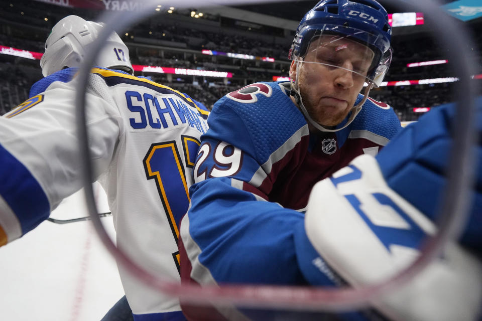 FILE - In this May 17, 2021, file photo, Colorado Avalanche center Nathan MacKinnon, right, checks St. Louis Blues left wing Jaden Schwartz in the corner in the first period of Game 1 of an NHL hockey Stanley Cup first-round playoff series in Denver. (AP Photo/David Zalubowski, File)