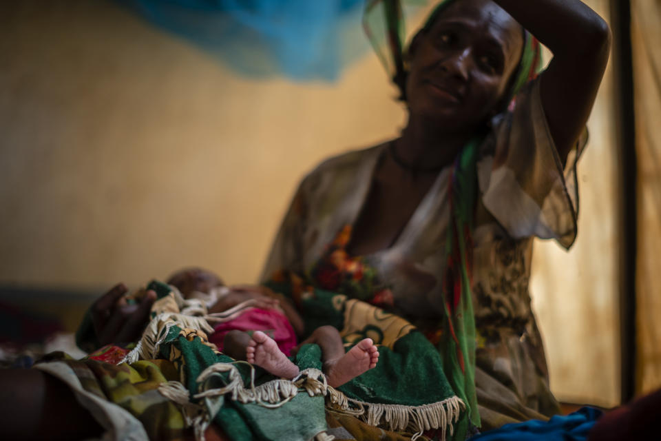 """Abeba Gebru, 37, from the village of Getskimilesley, sits with her malnourished daughter, Tigsti Mahderekal, 20 days old, in the treatment tent of a medical clinic in the town of Abi Adi, in the Tigray region of northern Ethiopia, on Tuesday, May 11, 2021. She had the baby at home and walked 12 days to get the famished child to a clinic in the northern Ethiopian region of Tigray. """"She survived because I held her close to my womb and kept hiding during the exhausting journey."""" (AP Photo/Ben Curtis)"""