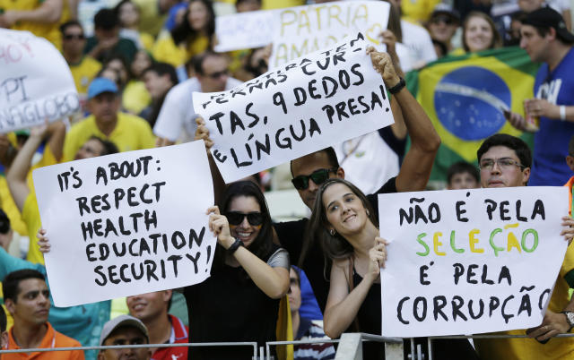 "Fans hold protest signs reading ""Not against the Brazilian team - against corruption"" during the soccer Confederations Cup group A match between Brazil and Mexico at Castelao stadium in Fortaleza, Brazil, Wednesday, June 19, 2013. (AP Photo/Natacha Pisarenko)"
