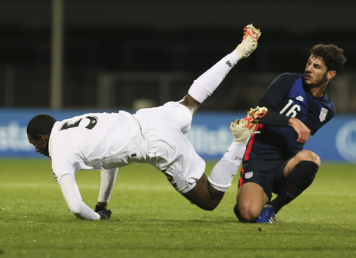 Panama's Abdiel Ayarza falls as he is tackled by United States' Johnny Cardoso during the international friendly soccer match between the USA and Panama at the SC Wiener Neustadt stadium in Wiener Neustadt, Austria, Monday, Nov. 16, 2020. (AP Photo/Ronald Zak)