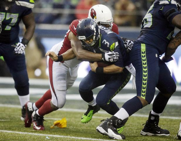 Arizona Cardinals defensive end Calais Campbell, left, sacks Seattle Seahawks quarterback Russell Wilson in the second half of an NFL football game, Sunday, Dec. 22, 2013, in Seattle. The Cardinals won 17-10. (AP Photo/Stephen Brashear)