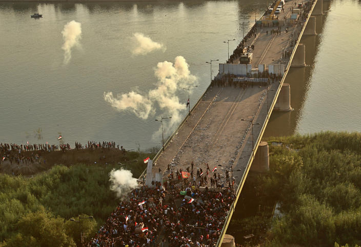 Security forces fire tear gas and close the bridge leading to the Green Zone during a demonstration in Baghdad, Iraq, Saturday, Oct. 26, 2019. (Photo: Hadi Mizban/AP)