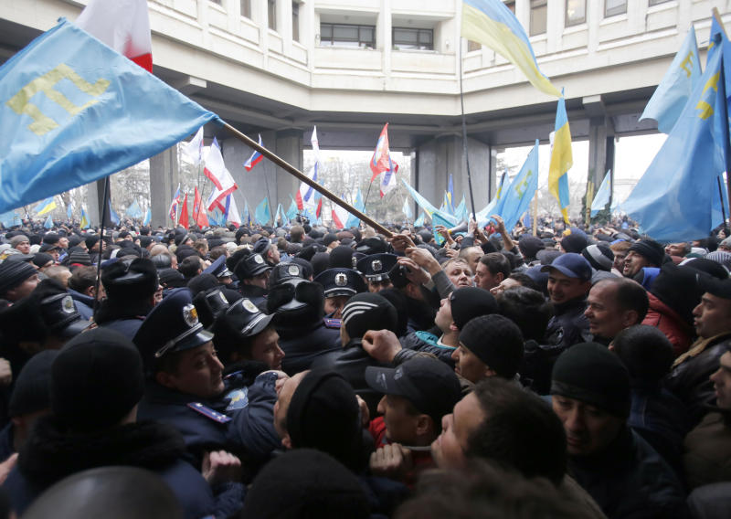 Crimean Tatars, right clash with police in front of a local government building in Simferopol, Crimea, Ukraine, Wednesday, Feb. 26, 2014. More than 10,000 Muslim Tatars rallied in support of the interim government. That group clashed with a smaller pro-Russian rally nearby. Fistfights broke out between pro- and anti-Russian demonstrators in Ukraine's strategic Crimea region on Wednesday as Russian President Vladimir Putin ordered massive military exercises just across the border. (AP Photo/Darko Vojinovic)