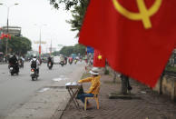 A lottery vender waits for customers under a national flag in Hanoi, Vietnam on Thursday, Aug. 6, 2020. Vietnamese health official said on Thursday the COVID-19 outbreak would peak in the coming ten days as the country reported another death and a score of new infections. (AP Photo/Hau Dinh)