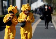 Visitors wearing protective face masks and Winnie the Pooh costumes, following an outbreak of the coronavirus, are seen outside Tokyo Disneyland in Urayasu