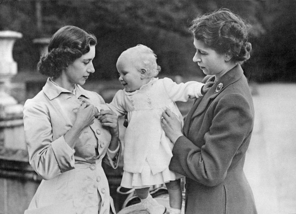 <p>Princess Margaret and then-Princess Elizabeth hold a young Princess Anne during a visit to Balmoral, the royals' Scottish estate.</p>