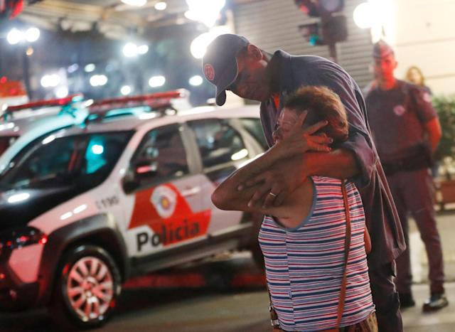 <p>Police officer comforts a woman near the site where a building collapsed in downtown Sao Paulo, Brazil May 1, 2018. (Photo: Leonardo Benassatto/Reuters) </p>
