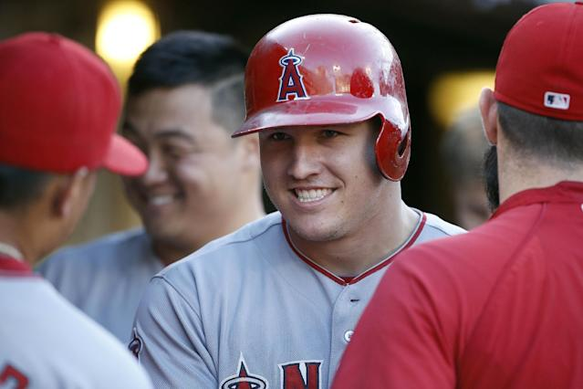 Los Angeles Angels' Mike Trout smiles as his congratulated in the dugout after he hit a solo home run against the Oakland Athletics in the sixth inning of a baseball game Sunday, Aug. 24, 2014, in Oakland, Calif. (AP Photo/Tony Avelar)
