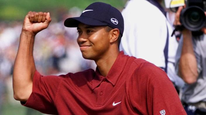 Tiger Woods celebrates by holding up a fist and smiling.