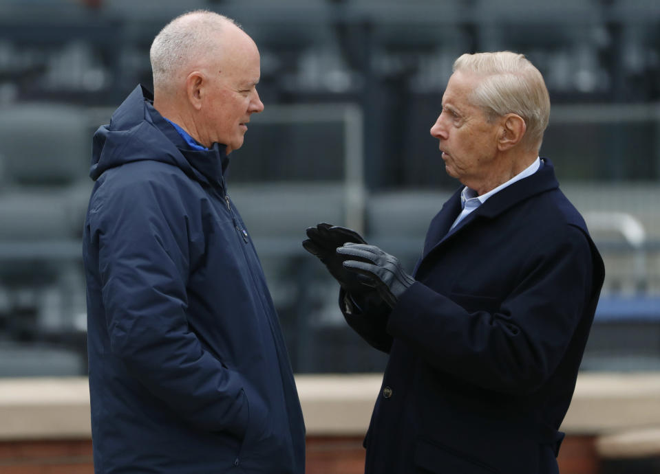 New York Mets general manager Sandy Alderson, left, listens to Mets majority owner and CEO Fred Wilpon on the field during the baseball team's workout Wednesday, March 28, 2018, in New York. The team's opening day is Thursday against the St. Louis Cardinals. (AP Photo/Kathy Willens)
