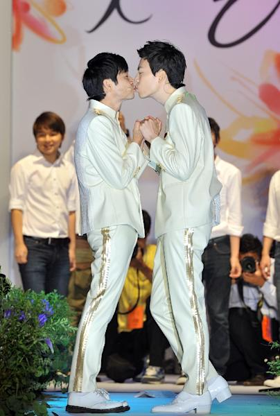 Film director Kim Jho Gwang-Soo (L) kisses his partner Kim Seung-Hwan during their wedding in central Seoul on September 7, 2013 (AFP Photo/Jung Yeon-Je)