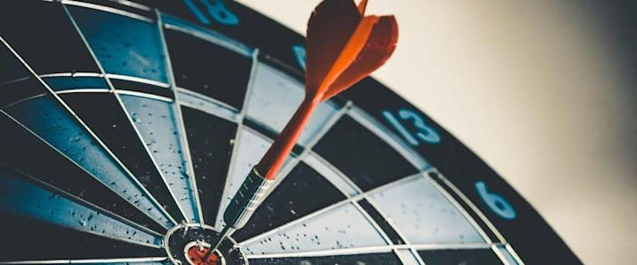 Close up shot of the dart arrow hit on bulleyes of dartboard to represent that the business reached the target of company with dark tone picture style. Target and goal as concept.