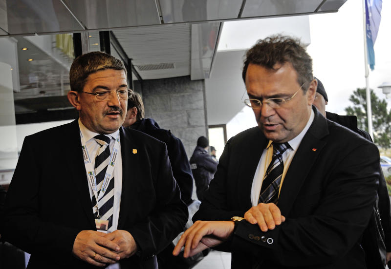 German interior minister Hans-Peter Friedrich , right, looks at his watch next to Mecklenburg Western-Pomerania interior minister Lorenz Caffier , left, as they arrive at a meeting with interior ministers of the 16 German states in Warnemuende, eastern Germany Wednesday, Dec. 5, 2012.  German security officials are moving toward a new attempt to ban the country's only significant far-right party, after meticulously collecting new evidence in an effort to avoid a repeat of the debacle when they tried to ban it in 2003.   The interior ministers of Germany's 16 states are expected to recommend Wednesday  evening pursuing a new ban of the National Democratic Party on allegations it promotes a racist, xenophobic, and anti-Semitic agenda in violation of the country's constitution.  Under the previous government of Chancellor Gerhard Schroeder, the country's Federal Constitutional Court rejected an attempt to ban the party after it turned out paid government informants within the NPD, as it known by its German initials, were partially responsible for the evidence against the party. (AP Photo/dapd/ Thomas Haentzschel)