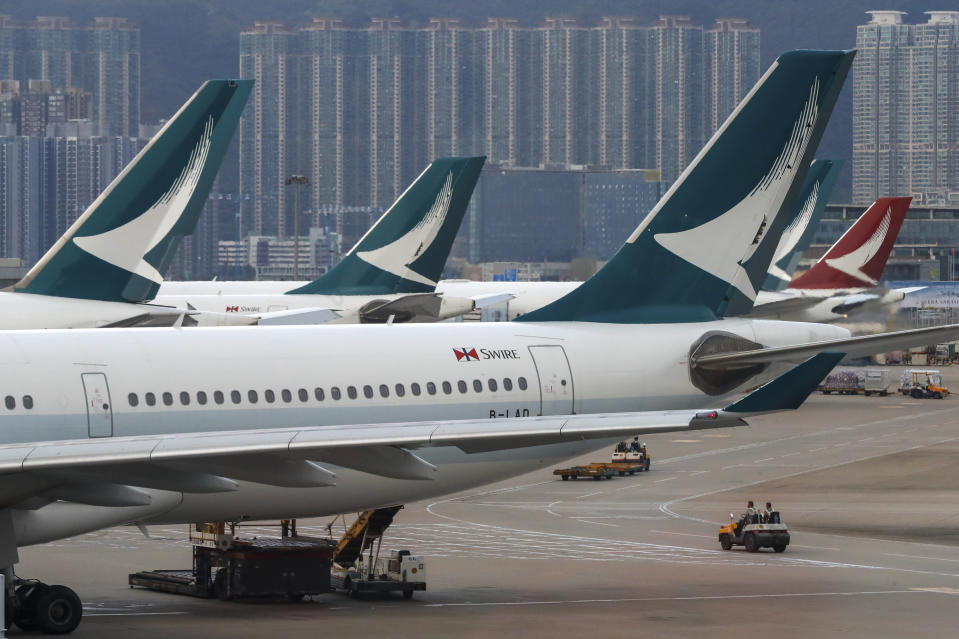 FILE - In this Aug. 12, 2019, file photo, ground crew drive past Cathay Pacific and Cathay Dragon Airways planes park at the Hong Kong International Airport. Hong Kong airline Cathay Pacific Airways on Wednesday, Oct. 21, 2020, said it would cut 8,500 jobs and shut down its regional airline unit in a corporate restructuring, as it grapples with the plunge in air travel due to the pandemic. (AP Photo/Vincent Thian, File)