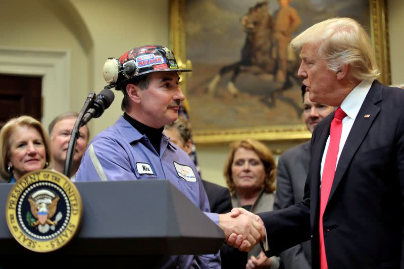 FILE PHOTO: FILE PHOTO: Michael Nelson, a coal miner worker shakes hands with U.S. President Donald Trump as he prepares to sign Resolution 38, at the White House in Washington, U.S.