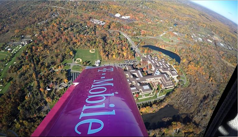 IMAGE DISTRIBUTED FOR T-MOBILE - A T-Mobile skywriter flies over Verizon's headquarters in Basking Ridge, NJ, Monday, Oct. 26, 2015, sending a message on behalf of consumers to abolish overages in the wireless industry. Last year alone, AT&T, Verizon, and Sprint charged $1.5 billion in overage penalties from their customers, and over 325,000 people signed T-Mobile President and CEO John Legere's Change.org petition to abolish overages. (Diane Bondareff/AP Images for T-Mobile)