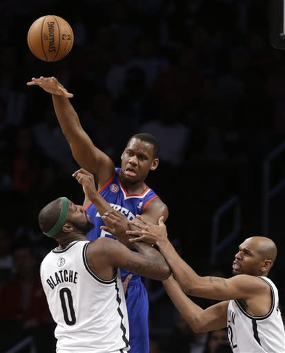 Philadelphia 76ers center Lavoy Allen (50) passes over the defense of Brooklyn Nets center Andray Blatche (0) and forward Jerry Stackhouse (42) in the first half of an NBA basketball game, Tuesday, April 9, 2013, in New York. (AP Photo/Kathy Willens)
