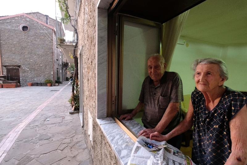 Antonio Vassallo, 100, and his wife Amina Fedollo, 93, pose for a photo at their house in Acciaroli, southern Italy