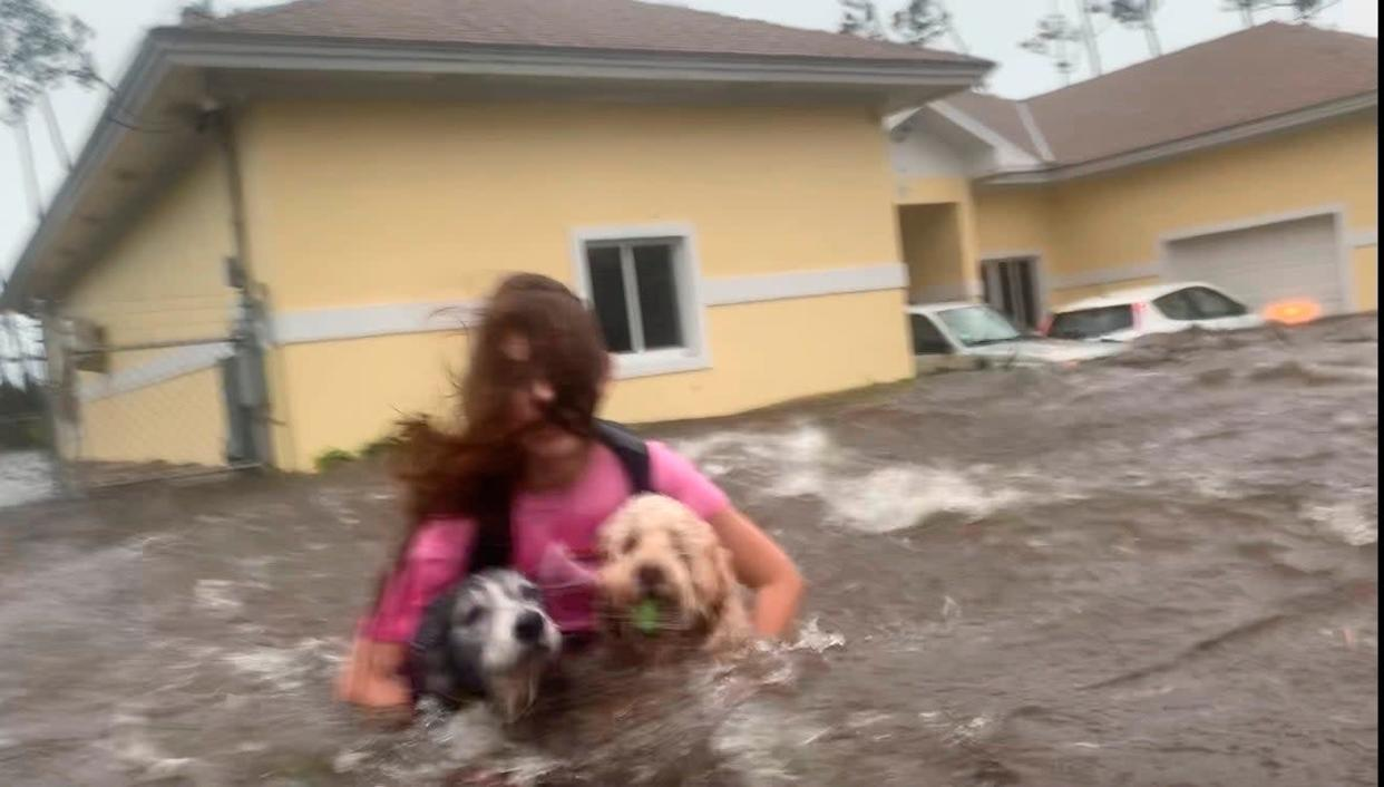 Julia Aylen wades through water carrying her dogs after her home in Freeport, Bahamas, was flooded by Hurricane Dorian: AP