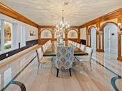 <p>Hand-crafted wood paneling and mouldings create an elegant feel in the formal dining room—and the floor gives a hat tip to basketball.</p>