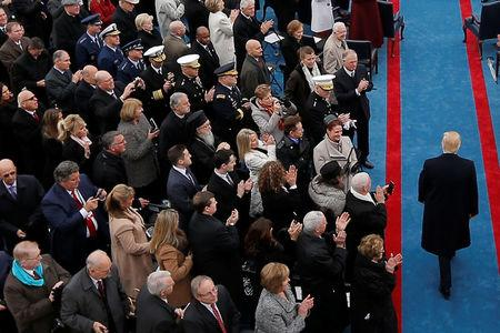 FILE PHOTO: Former National Security Adviser Michael Flynn (Upper L) looks down at a mobile phone as U.S. President-elect Donald Trump arrives for the inauguration ceremonies on the West front of the U.S. Capitol in Washington, U.S., January 20, 2017. REUTERS/Brian Snyder/File photo