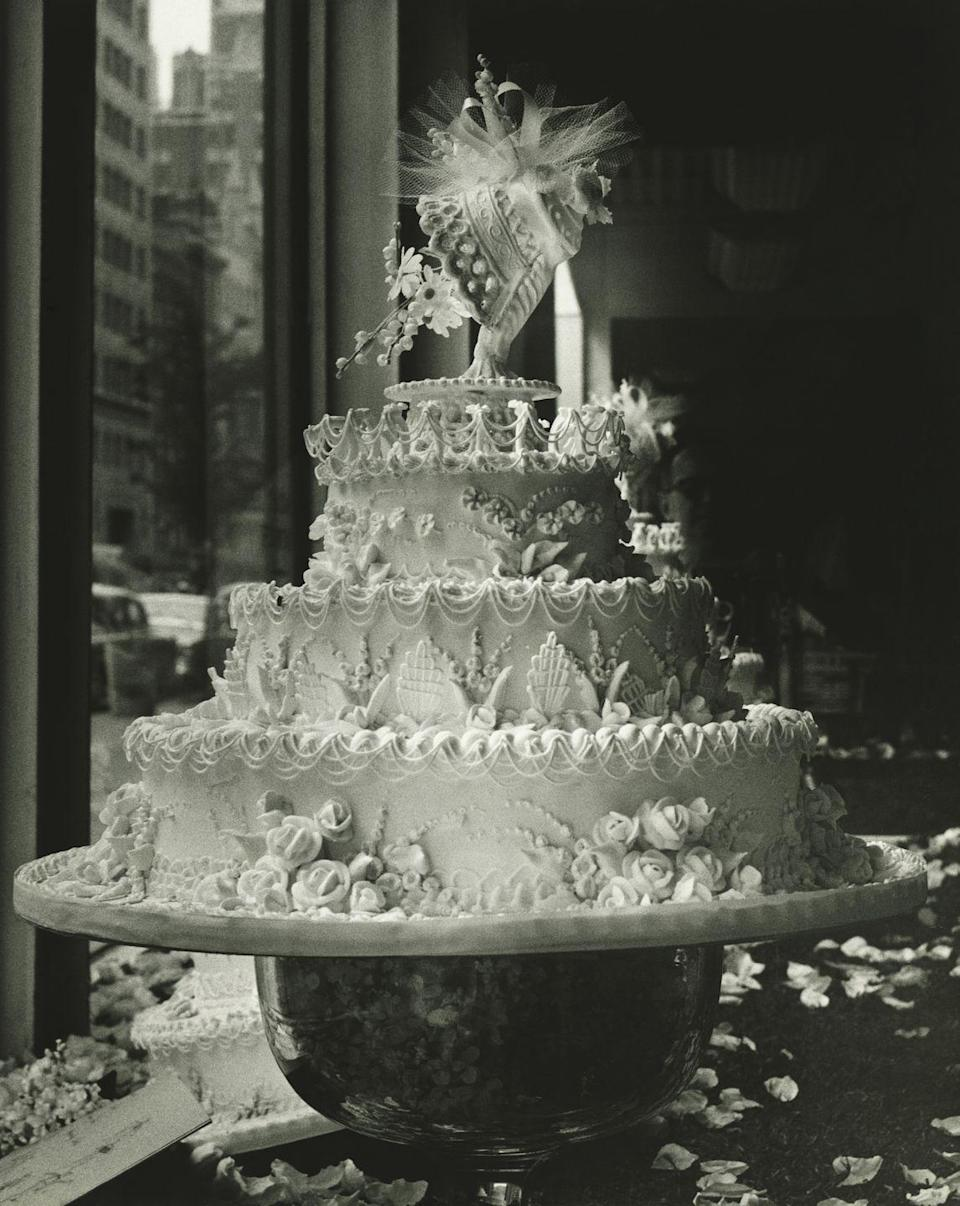 """<p>Wedding cakes were initially thought of as a luxury item, as the refined sugars needed to make <a href=""""http://www.gastronomica.org/wedding-cake-a-slice-history/"""" rel=""""nofollow noopener"""" target=""""_blank"""" data-ylk=""""slk:pure white frosting"""" class=""""link rapid-noclick-resp"""">pure white frosting</a> were very expensive. In fact, the term """"royal icing"""" came about thanks to Queen Victoria and her extravagant, multitiered white-frosted wedding cake. Pictured here is a wedding cake from 1930. </p>"""