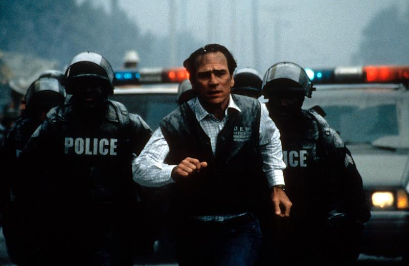 Tommy Lee Jones runs with the police behind him in a scene from the film 'Volcano', 1997. (Photo by 20th Century-Fox/Getty Images)