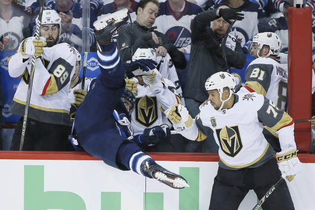 Winnipeg Jets' Blake Wheeler gets dumped over the boards by Vegas Golden Knights' Ryan Reaves (75) during the first period of Game 1 of the NHL hockey playoffs Western Conference final, Saturday, May 12, 2108, in Winnipeg, Manitoba. (John Woods/The Canadian Press via AP)