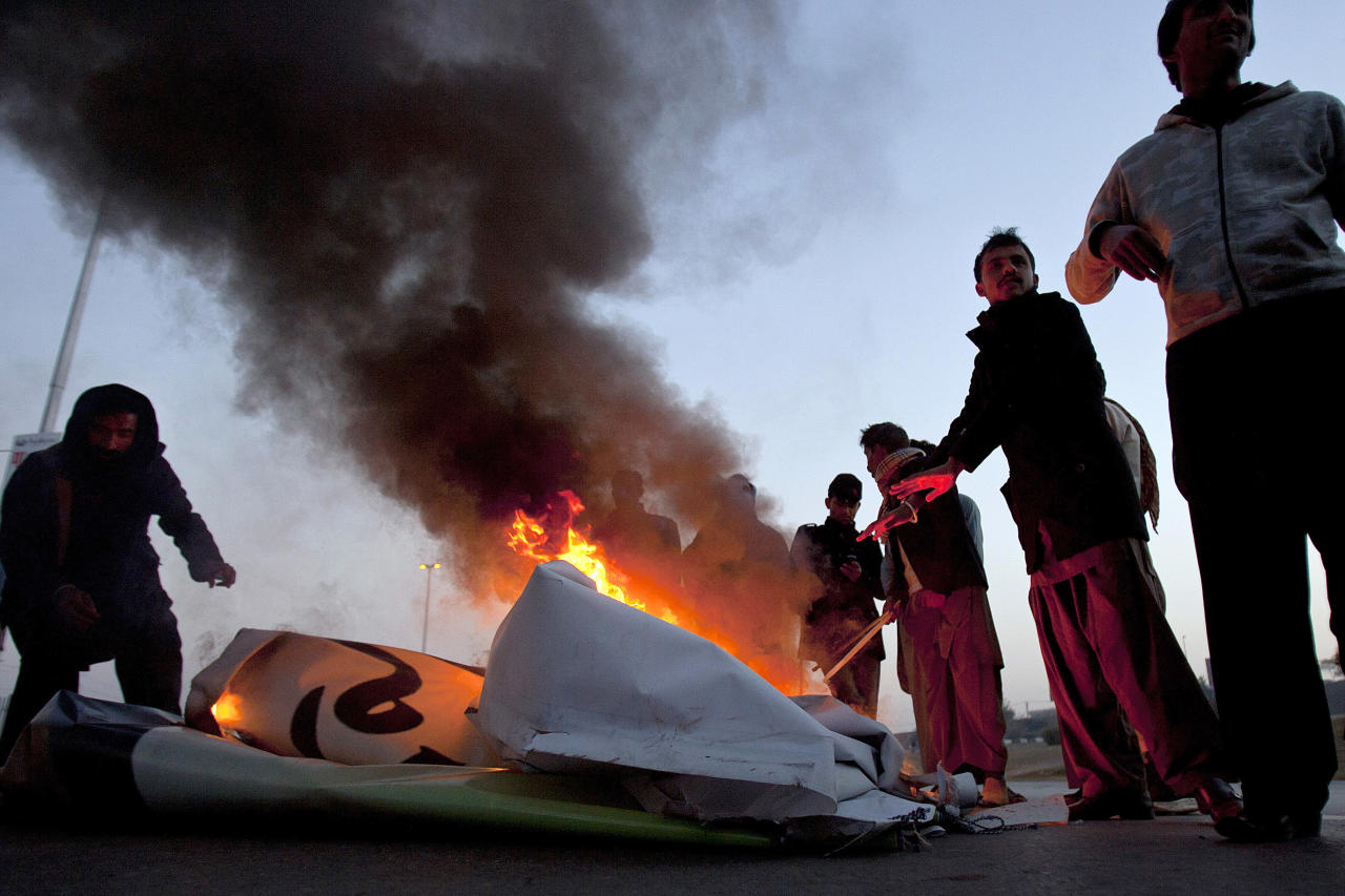 Pakistani Shiite Muslims gather around a burning billboard after setting it on fire during a rally to condemn Thursday's deadly bombings in Quetta, in Islamabad, Pakistan, Sunday, Jan. 13, 2013. Thousands of Pakistani Shiites protested in southwestern Pakistan for a third day blocking a main road with dozens of coffins of relative killed in explosions to demand better security from the government. (AP Photo/Anjum Naveed)