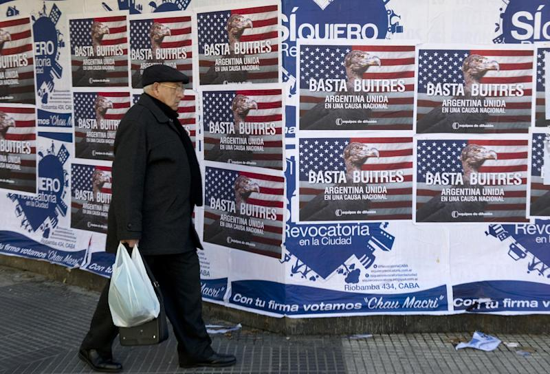 """A man passes by posters on a wall against """"vulture funds"""", in Buenos Aires on June 18, 2014 (AFP Photo/Alejandro Pagni)"""
