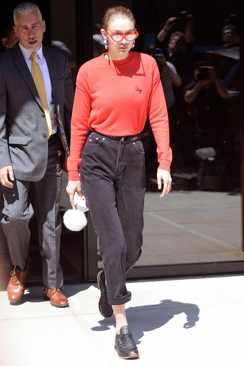 <p>In a red customized Rebecca Minkoff Gigi sweater, red Adam Selman x Le Specs Last Lolita eye sunglasses, high-waisted black jeans, Reebok sneakers and gold hoop earrings while out in New York.</p>