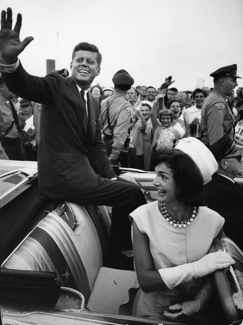 <p>Jackie and her husband wave to crowds in Massachusetts during the beginning of his presidential campaign. </p>