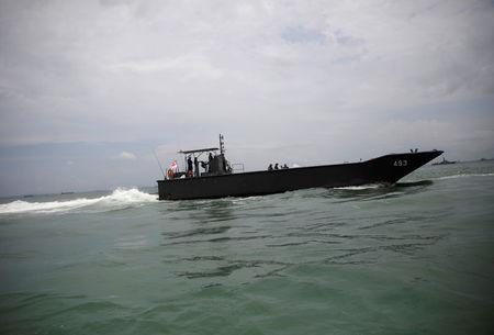 A Singapore patrol boat is seen in the waters near USS John S. McCain after a collision, in Singapore waters August 21, 2017. REUTERS/Ahmad Masood
