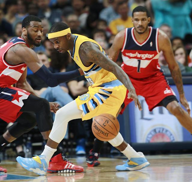 Denver Nuggets guard Ty Lawson, center, loses control of the ball as Washington Wizards guard John Wall, left, and forward Trevor Ariza cover in the first quarter of an NBA basketball game in Denver on Sunday, March 23, 2014. (AP Photo/David Zalubowski)