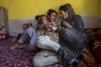 A transgender Kashmiri Khushi Mir, left, relaxes with friends at the end of a meeting of community members in the outskirts of Srinagar, Indian controlled Kashmir, Friday, June 4, 2021. Khushi, along with four young boys, have begun a volunteer group to distribute food kits to the transgender community. (AP Photo/ Dar Yasin)
