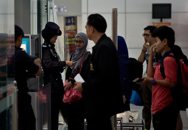 A Malaysian Police officer checks paseengers' passports in the departure hall of Kuala Lumpur International Airport on March 10, 2014