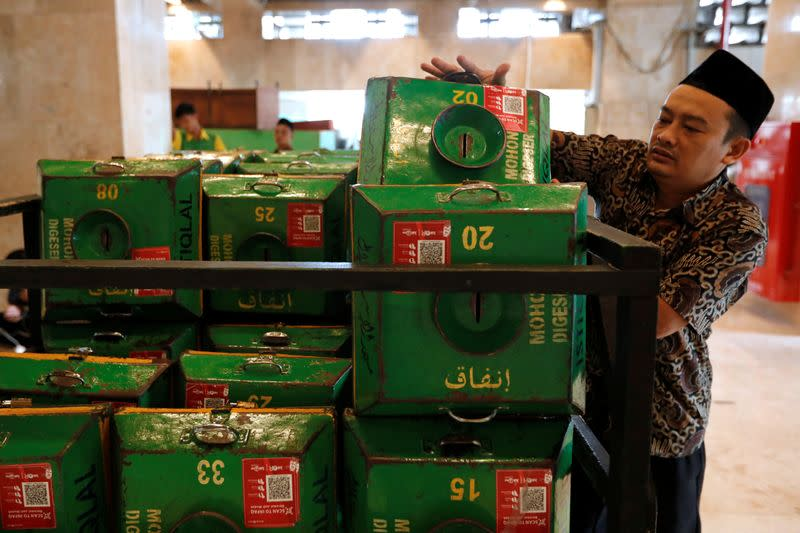A volunteer collects alms boxes with QR codes and stacks them on a cart after Friday prayers at Istiqlal mosque in Jakarta