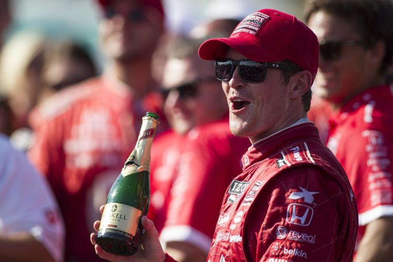 Scott Dixon, of New Zealand, holds a bottle of sparkling wine as he stands in Victory Circle after winning the IndyCar auto race in Toronto on Sunday, July 14, 2013. (AP Photo/The Canadian Press, Chris Young)