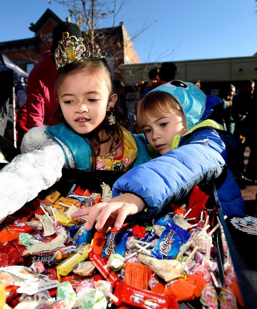 BOULDER, CO – OCTOBER 31, 2018: Sophie Hendrix, 6, anther brother Richard, 4, grab some candy from a basket while trick-or-treating during the Munchkin Masquerade on the Pearl Street Mall on Wednesday in Boulder.(Photo by Jeremy Papasso/Digital First Media/Boulder Daily Camera via Getty Images)