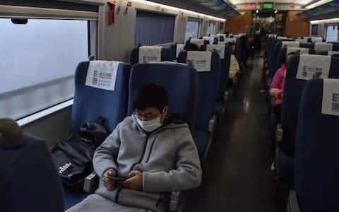 <span>A young man wearing a protective facemask sits on a train usually full with passengers ahead of the Lunar New Year as he travels from the Chinese city of Shanghai to his hometown of Wuhan</span> <span>Credit: AFP </span>