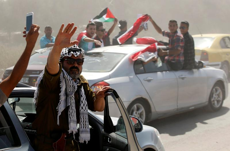 People celebrate as Palestinian Prime Minister Rami Hamdallah arrives to take control of Gaza from the Islamist Hamas group, in the northern Gaza Strip October 2, 2017. REUTERS/Mohammed Salem