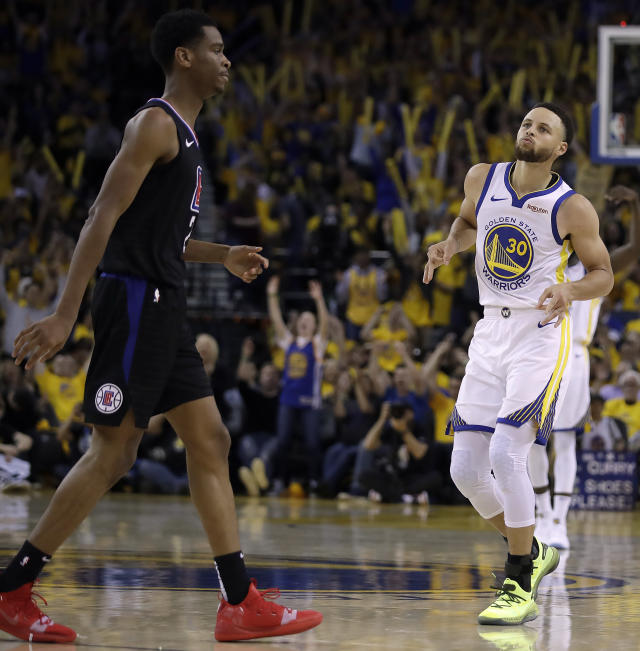 Golden State Warriors' Stephen Curry, right, celebrates after scoring in front of Los Angeles Clippers' Shai Gilgeous-Alexander during the second half in Game 1 of a first-round NBA basketball playoff series Saturday, April 13, 2019, in Oakland, Calif. (AP Photo/Ben Margot)