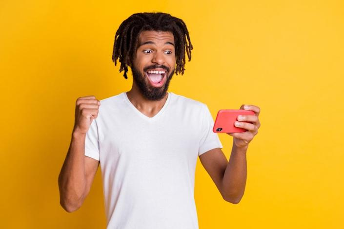Photo of funky gamer dark skin guy hold telephone playing new video game pass new level isolated yellow color background.