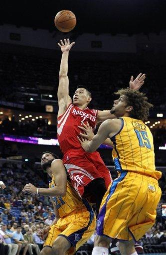 Houston Rockets guard Jeremy Lin (7) drives to the basket between New Orleans Hornets center Robin Lopez (15) and guard Greivis Vasquez (21) in the first half of an NBA basketball game in New Orleans, Friday, Jan. 25, 2013. (AP Photo/Gerald Herbert)